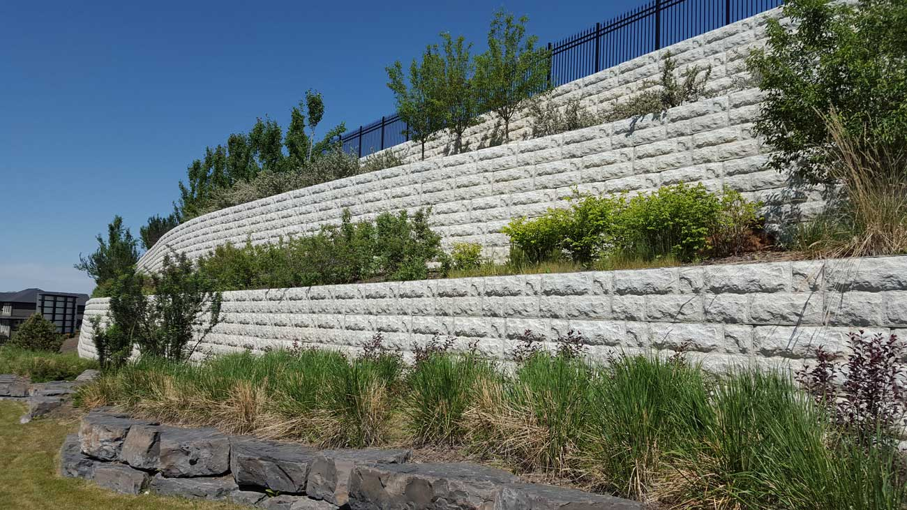 MagnumStone Block Retaining Wall Random Boulder Face With Shrubs