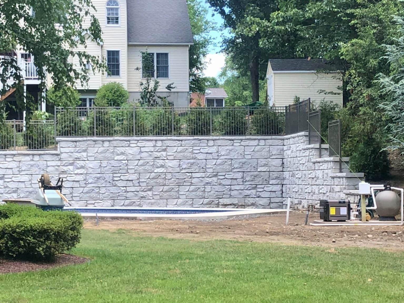 MagnumStone 12 foot retaining wall in a backyard, allowing room for a swimming pool. The wall features an inside corner and top of wall details like caps, fence posts, and step ups.