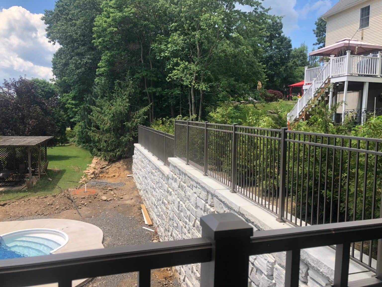View from on top of a MagnumStone wall showing fenceposts and fence